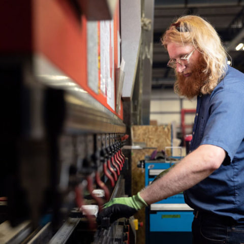 Man with long hair working on red machine in factory.