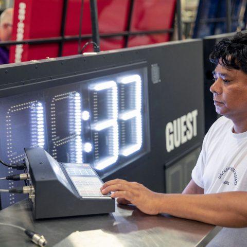 Man working on building Scoreboard in factory.