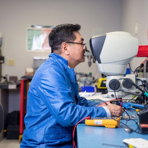 Man working with wires and looking through a microscope