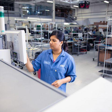 Women working on machine in factory
