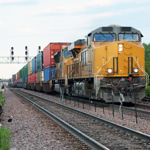 Two yellow locomotives and double stack freight train