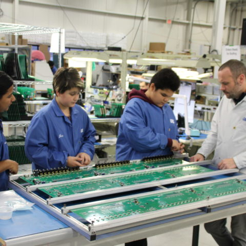 Students in blue lab coats learning about circut boards