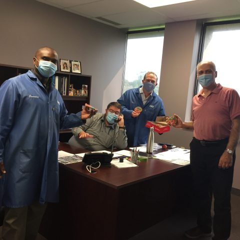 men in an office wearing masks and having a meeting