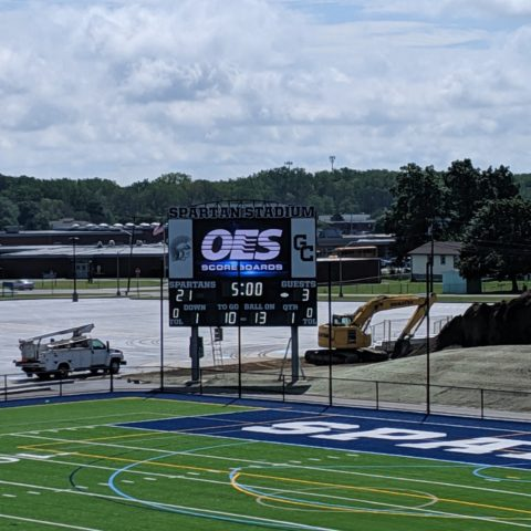 View of a football field with the view of the scoreboard in the background.