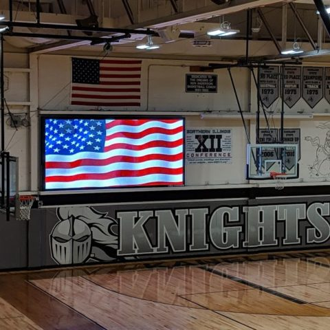 video scoreboard ishowing the american flag in the gym at Kaneland high school