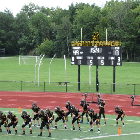 scoreboard behind football players