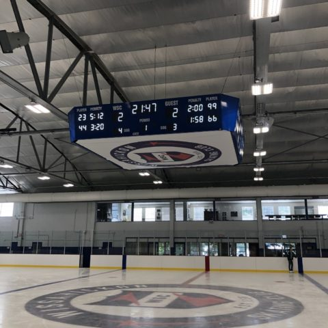 small four sided hockey scoreboard at centre ice of an arena