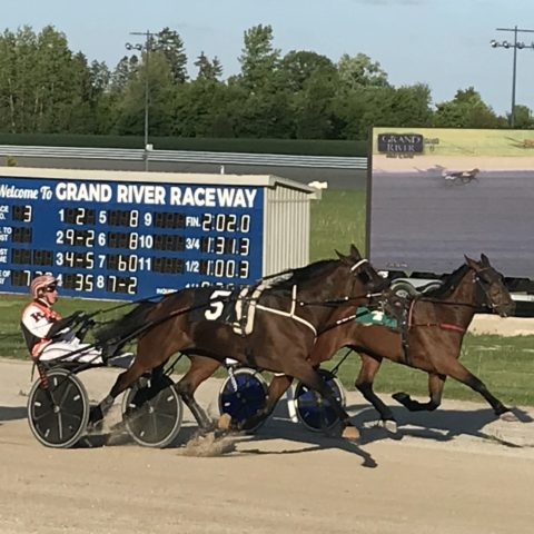 showing a harness horse race in action with the tote board and a video display on a trailer in the background