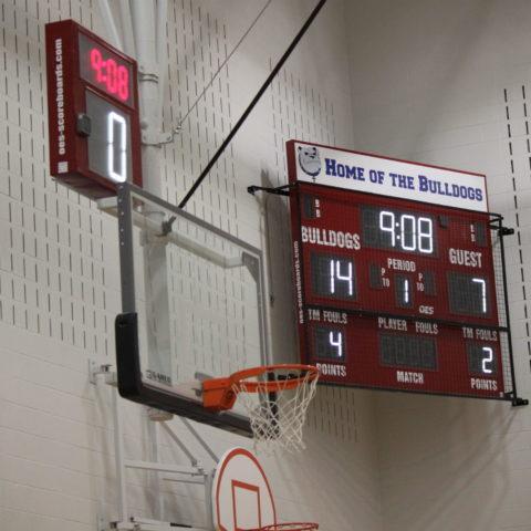 An indoor basketball scoreboard with a shot clock above the basketball net.
