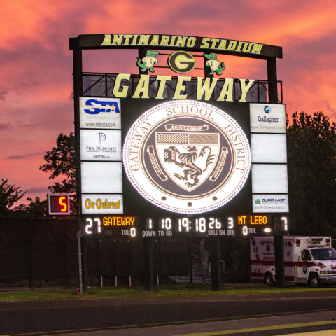 The video display at Gateway High School with the sun setting behind it. Sky is pink and orange in color.
