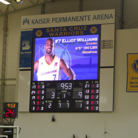 Basketball scoreboard with picture of player on the screen.