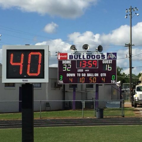 play clock on a football field with a scoreboard in the background