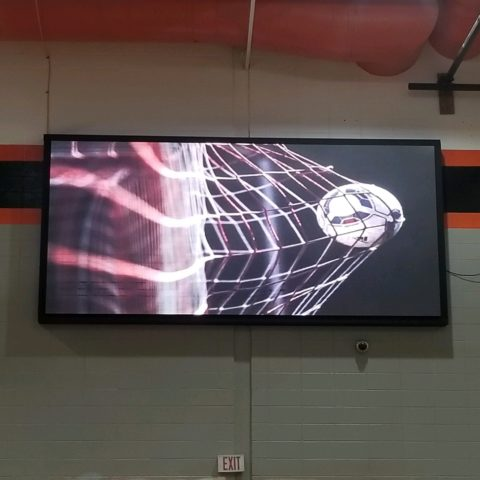 Scorebored on gym wall with picture of soccer ball going into net.