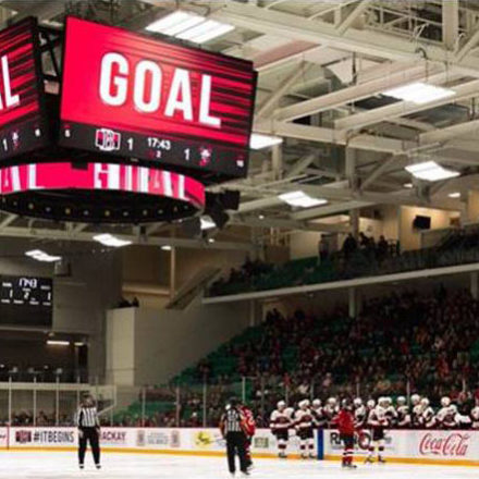 Hockey arena with large video scoreboard displaying 'goal'.