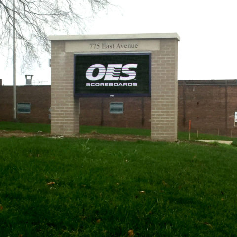 The OES logo displayed on an LED scoreboard outside.