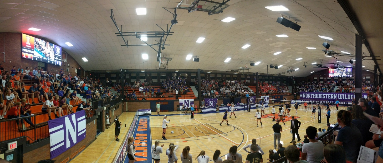 Panaramic view of a high school gym where a basketball game is being played