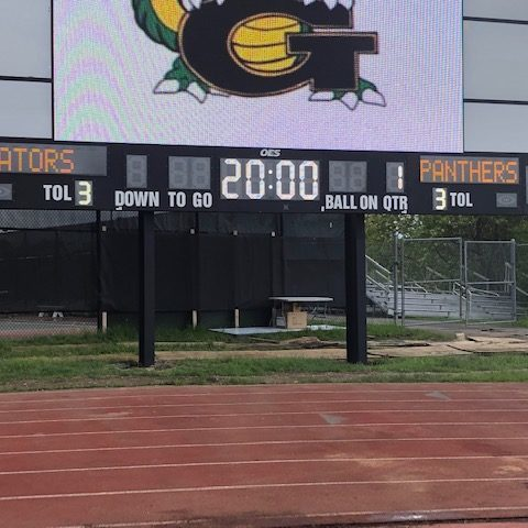 close up of the black scoreboard with white digits under the video screens of a high school football scoreboard