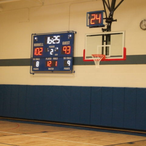 An indoor basketball scoreboard with a shot clock above the basketball net.