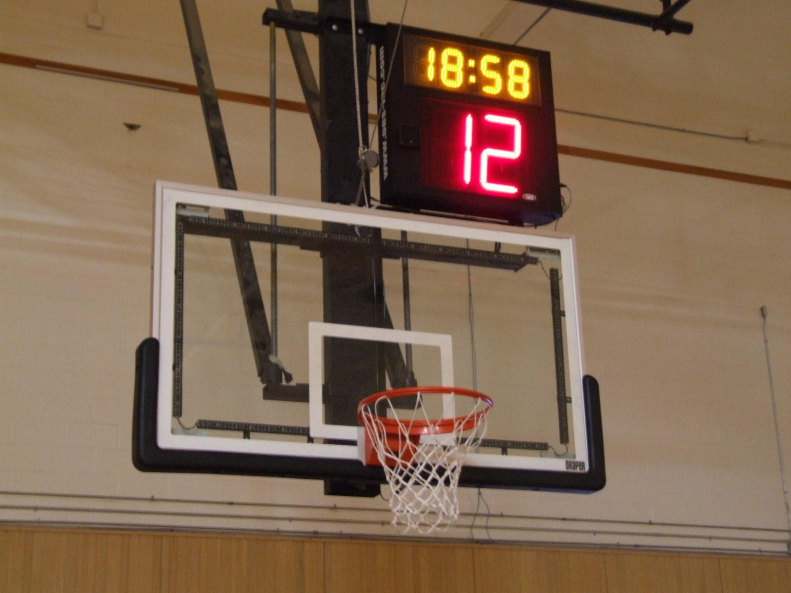 A shot clock above an indoor basketball net.