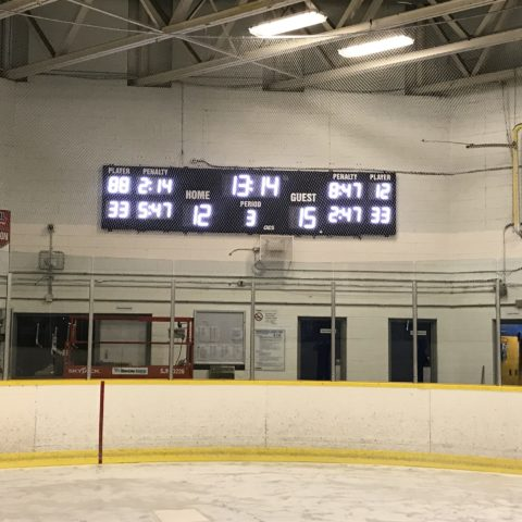 hockey scoreboard behind netting