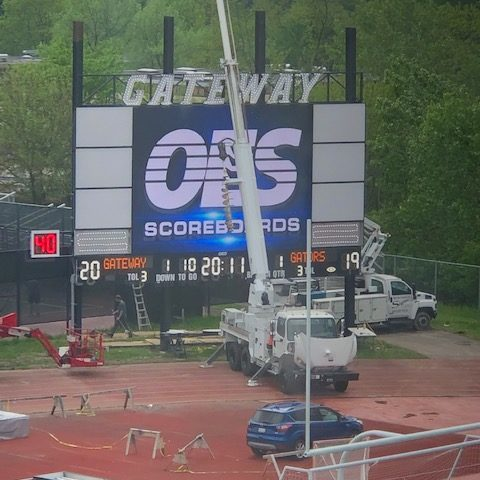 A crane lifting the truss onto the top of a video scoreboard