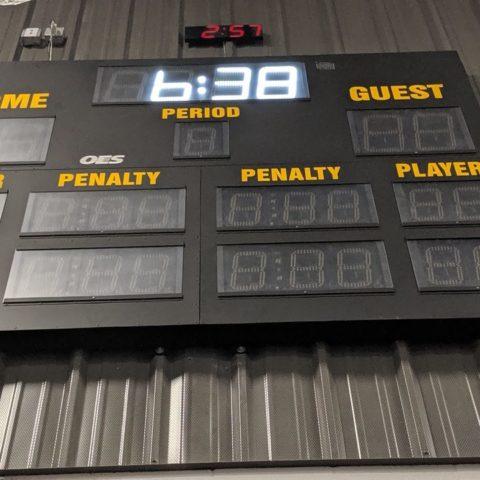 unlit scoreboard on a wall showing 6 o'clock