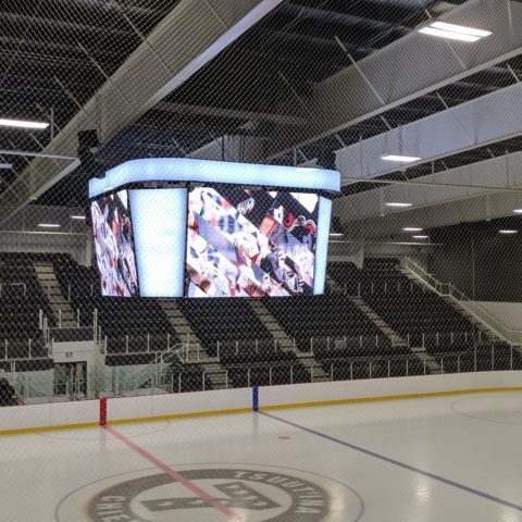 four sided video scoreboard at centre ice in an arena turned on and showing a hockey game