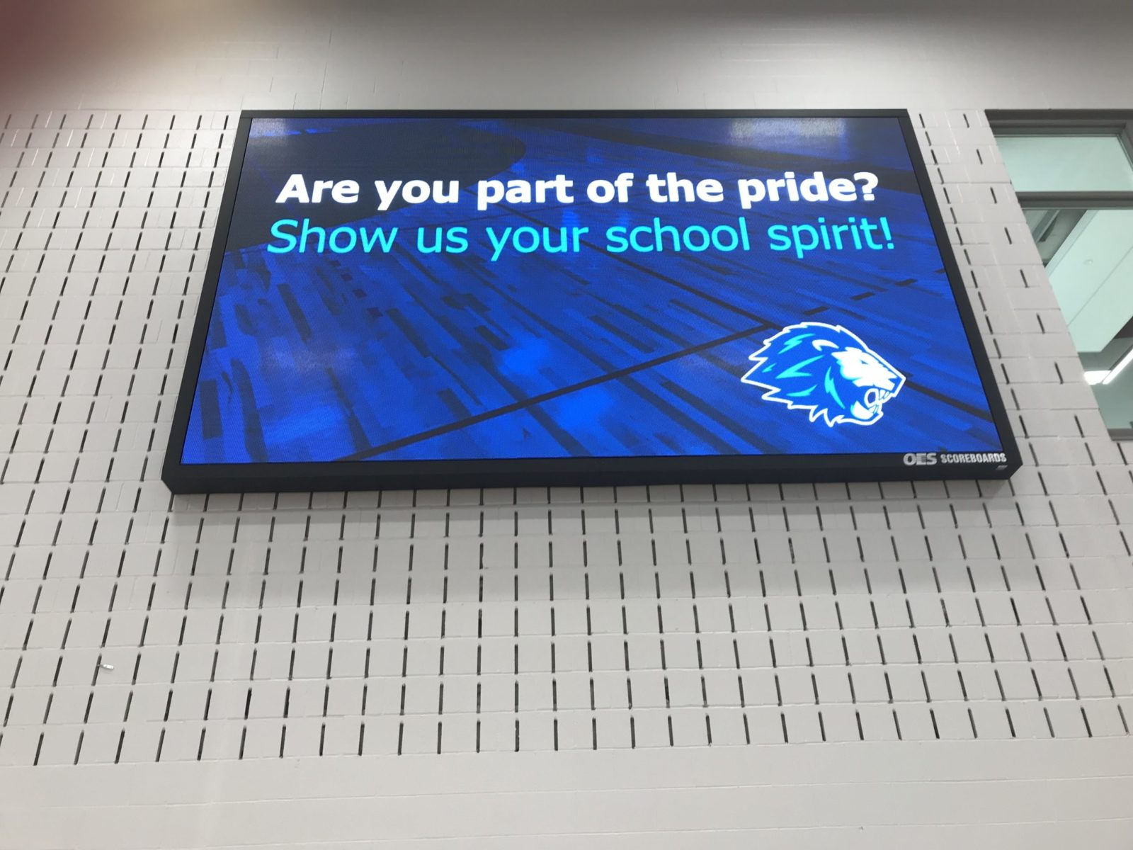 "An indoor scoreboard with words ""are you part of the pride?'"