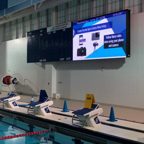 Video display beside a scoreboard in a swimming pool facility