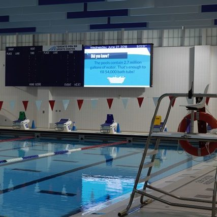 video display on a wall with a swimming pool and lifeguard chair in the foreground