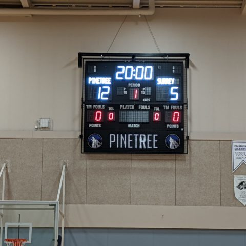 small basketball scoreboard in a gym