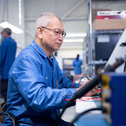 Older man working with wires on factory floor.