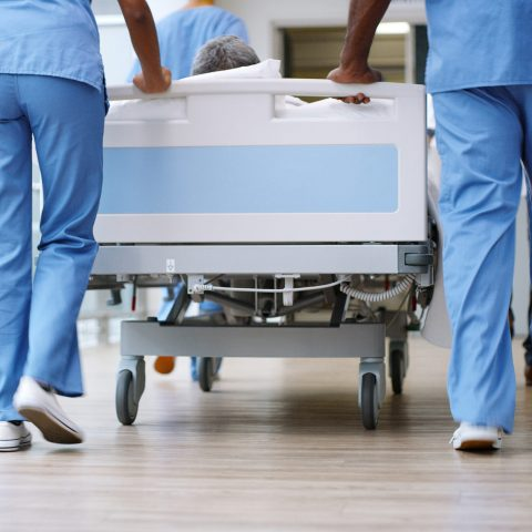Hospital workers pushing bed down a medical building hallway.