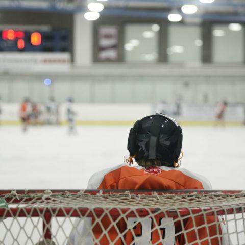 Child hockey goalie in net facing opposition on ice rink