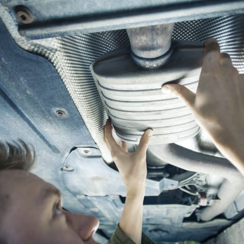 Male mechanic replacing exhaust pipe under car